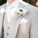 The groom wore a light grey three-piece suit accessorized with a white satin tie, a white pocket square, and a white anemone and dusty miller boutonniere.  Ceremony Venue: Mural Room at The Santa Barbara Courthouse  Reception Venue: Canary Hotel  Groom's Attire: J.Crew  Floral Designer: ella & louie