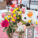The tables were decorated in pink cloths, lace crocheted doilies, silver framed table numbers, and vibrant arrangements of roses, poppies, sweet peas, anemones, and button mums.  Reception Venue:Canary Hotel  Floral Designer:ella & louie