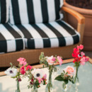 The lounge area featured wicker sofas with black and white striped cushions and mismatched glass bud vases filled with sweet peas, anemones, and roses.  Reception Venue:Canary Hotel  Floral Designer:ella & louie