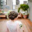 She wore a satin a-line wedding gown with an illusion necklace, accessorized with her hair in a twisted updo.   Dress Designer: Reem Acra from Blue Sky Bridal  Hair Stylist: Kate DeMotts  Makeup Artist: Kristen Lawson  Floral Designer: Daphne Darst of D Designs
