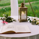 A sweet welcome table featuring a romantic iron garden lantern, a storybook guest book, and bundles of eucalyptus and blooms.  Reception Venue: Tuckahoe Plantation  Event Planner: A Grand Affair  Floral Designer: Petals & Twigs