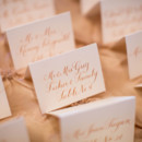 Guests found their seats with these gorgeous gold calligraphed escort cards.  Ceremony Venue:Georgetown Lutheran Church  Reception Venue:Army Navy Country Club  Event Planner:Karson Butler Events  Calligraphy:Laura Hooper Calligraphy  Linens & Custom Chair Backs:i do linens