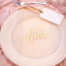The tablescapes featured blush satin linens, classic ivory dinner plates, and gold calligraphed place cards.  Reception Venue:Army Navy Country Club  Event Planner:Karson Butler Events  Calligraphy:Laura Hooper Calligraphy  Linens & Custom Chair Backs:i do linens  Rentals: Party Rental andDC Rental