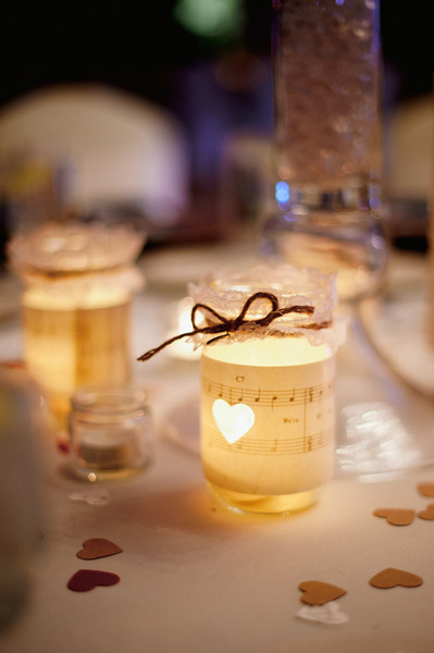 Heart-shaped confetti and votive candles in mason jars wrapped with sheet music also decorated the tables.   Reception Venue: Versailles Ballroom at the Ramada of Toms River