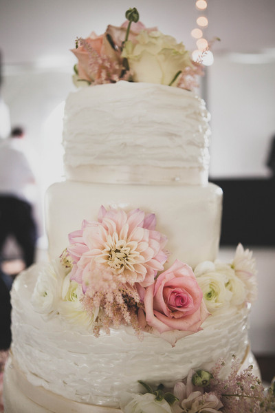 Attractive Roses, Ranunculuses And Cafe Au Lait Dahlias Garnished The Three Tier  Buttercream Cake.