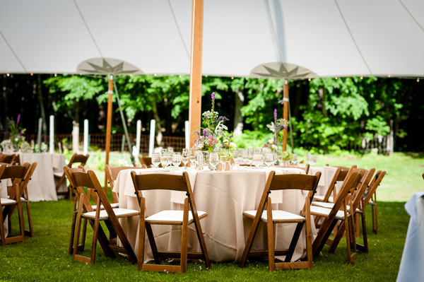 Guests Dined Under A Tent Outside At Round Tables In Wooden Folding Chairs Venue