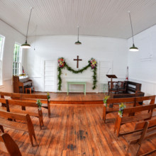 <strong class='info-row'>Thirteenth Moon Photography LLC</strong> <div class='info-row description'><html>  <head></head>  <body>    This turn-of-the-century chapel, which is situated in the middle of the woods, was originally a schoolhouse. It only holds 50 guests, so the remainder were seated outside and watched through the windows.       </body> </html></div>