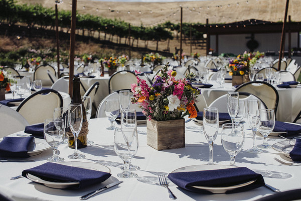Guests sat at round tables covered in white linens featuring wooden boxes filled with colorful blooms & California Centerpiece Centerpieces Greenery Outdoor Reception Place ...