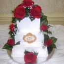 This cake is buttercream with a fondant plaque and silk red roses of the Brides choosing.