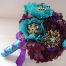 Lovely and romantic quality silk bouquet created with eggplant hydrangea, turquoise poppy flowers, turquoise and purple satin ribbon roses. Turquoise rhinestone and crystal brooches are interspersed throuout the bouquet. The handle is wrapped in an turquoise satin ribbon with a purple ribbon criss cross. This bouquet is available in other colors.