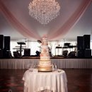 Their beautiful wedding cake with the chandelier in the background.