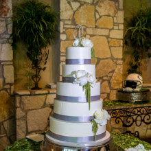"<strong class='info-row'>Svetlana Photography</strong> <div class='info-row description'><html>  <head></head>  <body>    A show-stopping five-tier wedding cake was adorned with flowers and silver ribbons.   Venue:    <a href=""https://www.weddingwire.com/biz/the-vista-on-seward-hill-austin/8620a87097a99c38.html"" target=""_blank"">The Vista on Seward Hill</a>  Floral Design:    <a href=""https://www.weddingwire.com/biz/flora-fetish-llc-austin/41aa20526a6d572e.html"" target=""_blank"">Flora Fetish, LLC.</a>  Cake:    <a href=""https://www.weddingwire.com/biz/simon-lee-bakery-pflugerville/e28b94b9588e074b.html"" target=""_blank"">Simon Lee Bakery</a>   </body> </html></div>"