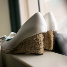 """<strong class='info-row'>Pond Photography</strong> <div class='info-row description'><html>  <head></head>  <body>    The bride donned white wedges with sparkly gold heels.     <span class=""""s1"""">Event Planner: <span class=""""s2""""><a href=""""https://www.weddingwire.com/biz/madison-sanders-events-liberty/bfd7956686c7ed3d.html"""">Madison Sanders Events</a></span></span>     <span class=""""s3"""">Bridal Shoes: Shoes of Prey</span>   </body> </html></div>"""