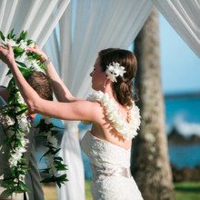 "<strong class='info-row'>Joanna Tano Photography</strong> <div class='info-row description'><html>  <head></head>  <body>    The couple exchanged the leis during the ceremony.  Venue: White Orchid Beach House from    <a href=""https://www.weddingwire.com/biz/a-white-orchid-wedding-inc-wailuku/613a4afe72f6cb8d.html"" target=""_blank"">A White Orchid Wedding, Inc.</a>  Hair and Makeup: Maui Beautiful Brides  Floral Design:    <a href=""https://www.weddingwire.com/reviews/teresa-sena-designs-kula/e68fec6403a0ee30.html"" target=""_blank"">Teresa Sena Designs</a>   </body> </html></div>"