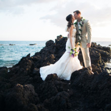 "<strong class='info-row'>Joanna Tano Photography</strong> <div class='info-row description'><html>  <head></head>  <body>    The newlyweds share a smooch on a rocky outcrop over the beach.  Venue: White Orchid Beach House from    <a href=""https://www.weddingwire.com/biz/a-white-orchid-wedding-inc-wailuku/613a4afe72f6cb8d.html"" target=""_blank"">A White Orchid Wedding, Inc.</a>  Hair and Makeup: Maui Beautiful Brides  Floral Design:    <a href=""https://www.weddingwire.com/reviews/teresa-sena-designs-kula/e68fec6403a0ee30.html"" target=""_blank"">Teresa Sena Designs</a>   </body> </html></div>"