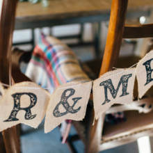 <strong class='info-row'>Erin Morrison Photography</strong> <div class='info-row description'><html>  <head></head>  <body>    The bride and groom decorated their chairs with a burlap bunting banner.  Venue: Tuckaway Cove   </body> </html></div>