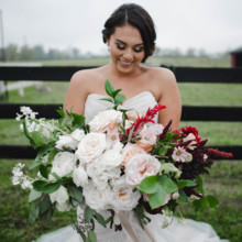 220x220 sq 1511989258953 bride smiling and admiring her bouquet