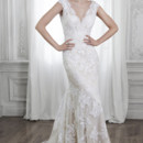 Shayla  Dreamy lace and tulle adorn this slim A-line wedding dress with dramatic V-neckline and back, accented with scallops and adorned with optional ribbon belt at the waist. Finished with covered button over zipper closure.
