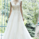 Bellissima  This tulle ballgown is the epitome of bridal bliss. Complete with dazzling Swarovski crystals accenting the bodice and illusion neckline, scalloped lace hemline, and delicate satin belt at the waist. Finished with pearl button over zipper and inner elastic closure.