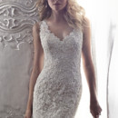 Breanna  Intricate all over lace adorns this sheath wedding dress with plunging, sleeveless neckline and sexy keyhole back. Finished with covered buttons over zipper back closure.