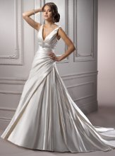 Maude - A3571  <br /> Stunning simplicity in an A-line silhouette sure to flatter any figure, this Soft Shimmer Satin sleeveless gown with deep V-neck features a rich Swarovski crystal brooch adorning the design with glamour and elegance. Finished with corset back closure.