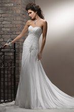 Mayla A subtle, yet splendid work of art in corded lace and Paris Chiffon draped over Romance Satin, this A-line gown is reminiscent of Grecian royalty. Details include a beaded motif with Swarovski crystals ornamenting the hip, scalloped, sweetheart neckline and corset closure.