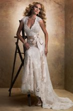 Bronwyn - 12623  A dreamy lace and tulle slim line gown with V-neckline and cap-sleeves features a separate slip gown of Vogue Satin to be worn below. The alluring open back is finished with a covered button over zipper closure. Includes a detachable ribbon belt.