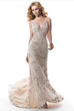 Gianna  Find a new gold standard with this slinky sheath featuring Midas worthy embellishments. Metallic embroidery coupled with linear beading create this stunning gown. Complete with a plunging V-neckline, accented with illusion tulle and zipper back closure.