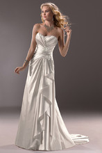 Aveline  Glamour and sophistication marry in this slim A-line gown of Demir Stretch Satin. Asymmetrical ruching on the bodice cascade into a side princess seam. Finished with signature corset back closure and accented with shimmering Swarovski crystals.