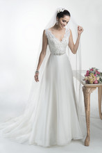 Debra Flowing Mystique organza A-line gown with corded Alençon lace bodice, available with glittering Swarovski crystal grosgrain ribbon belt. Finished with zipper over inner elastic and covered button closure.