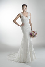 Melanie  Delicate corded lace on tulle skims the shoulders and neckline of this lightweight gown with attached Monroe slip dress while buttons trail a zipper closure accenting a deep, illusion back.