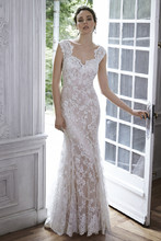 Londyn  Made from exquisite floral lace, this sheath gown is the epitome of romance. Complete with scalloped lace neckline and illusion lace back. Finished with covered button over zipper back closure.