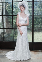 Luella Traditional lace with a dose of modern glamour is found in this sheath wedding dress, comprised of bold patterned lace, sweetheart neckline, and lace cap-sleeves, leading to a dramatic illusion lace scoop back. Finished with covered buttons over zipper closure.