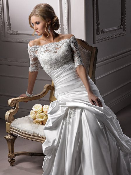 Symphony - A3635JK <br> Romance is redefined in this L'Amour Satin gown available with a stunning illusion lace jacket in which scalloped lace delicately dusts the shoulder of the portrait neckline. Three-quarter length sleeves and delicate button back closure complete this extraordinary accessory. The corset back fit and flare touts a sweetheart neckline with ruched bodice and skirt, softly caught up to reveal a beaded lace embellishment ornamented with Swarovski crystals.