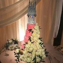 Photo of D & D Floral Design in Los Osos, CA - Gold dipped roses cascading down the wedding cake.